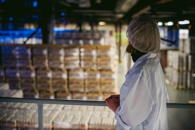 a woman employee of the warehouse. woman in a white robe, standing in the warehouse, on the background of rows of with the finished product, packaged in bottles of pallets